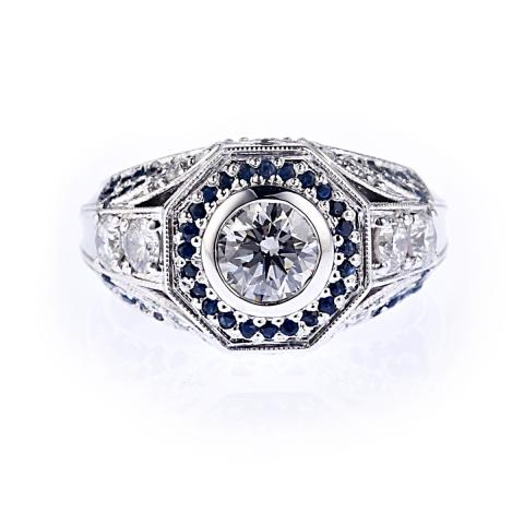 Bezel set central diamond with pave set sapphires surround. Further diamons set on shoulders of the ring. Outer edge is octagonal with a millgrain beading.