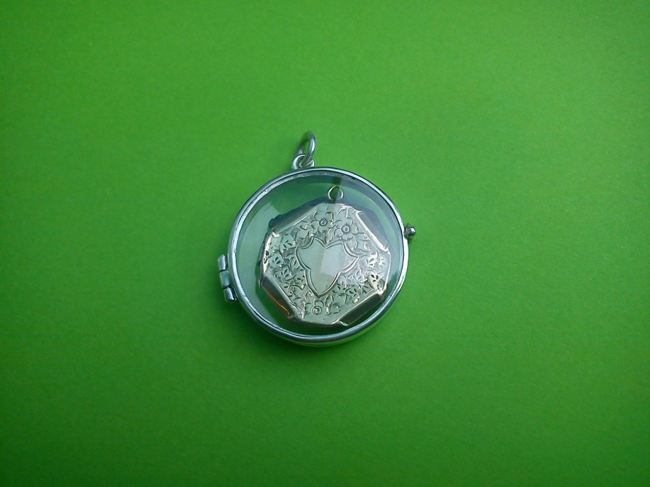 Outer locket made in silver with crystal watch cases so you can see the treasured inner locket which was badly damaged. Repurposed.