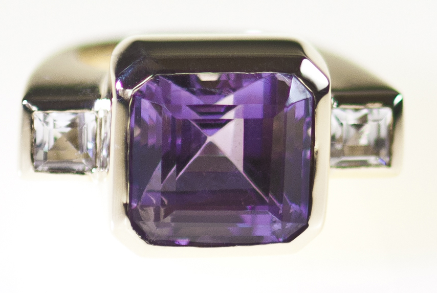 Large cushion cut amethyst bezel set and flanked by square cut white topaz, chunky modern design