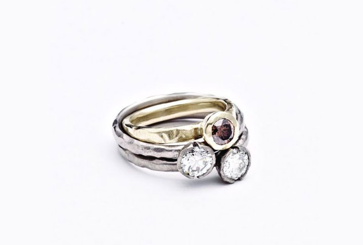 A set of three stacking ring with bezel set white and cognac diamonds, in white and yellow 18ct gold
